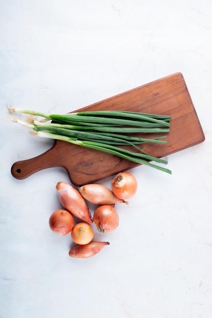 Vue De Dessus Des Légumes Comme L'oignon Vert Sur Une Planche à Découper Et L'échalote Sur Fond Blanc Avec Copie Espace Photo gratuit