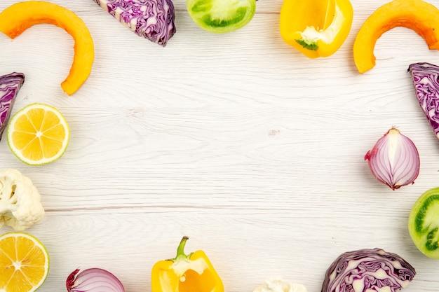 Vue De Dessus Légumes Coupés Chou Rouge Tomate Verte Citrouille Oignon Rouge Poivron Jaune Chou-fleur Citron Sur Une Surface En Bois Blanche Avec Place Libre Photo gratuit