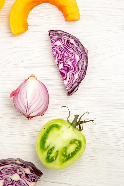 Vue De Dessus Légumes Coupés Chou Rouge Tomate Verte Citrouille Oignon Rouge Sur Surface Blanche Photo gratuit