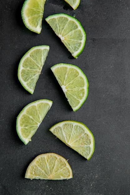 Vue De Dessus De Limes En Tranches Sur Une Surface Noire Photo gratuit