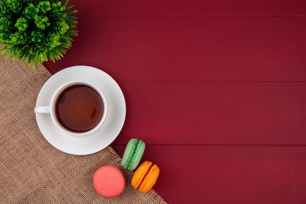 Vue De Dessus Des Macarons Colorés Avec Une Tasse De Thé Sur Une Serviette Beige Sur Une Surface Rouge Photo gratuit