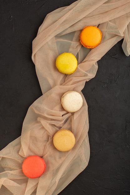 Une Vue De Dessus Macarons Français Colorés Délicieux Et Cuits Au Four Sur La Table Noire Biscuit Gâteau Biscuit Sucre Photo gratuit