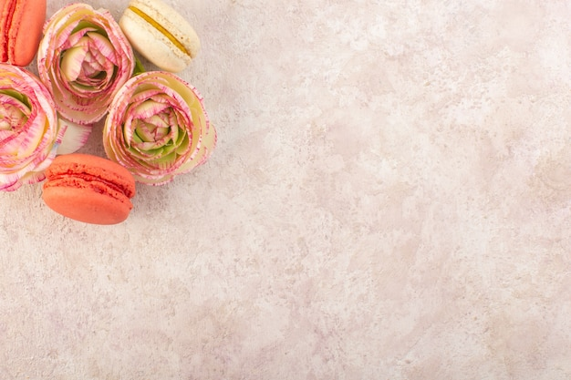 Une Vue De Dessus Macarons Français Colorés Avec Des Roses Fanées Sur Le Gâteau De Bureau Rose Biscuit Au Sucre Sucré Photo gratuit