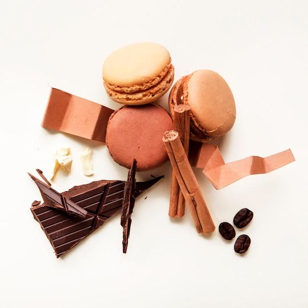 Vue de dessus des macarons; grains de café torréfiés; cannelle et barre de chocolat sur fond blanc Photo gratuit