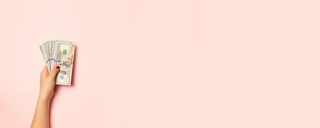 Vue de dessus une main féminine avec pile de billets d'un dollar d'argent sur rose Photo Premium