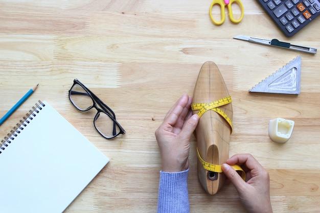 Vue de dessus de la main de femme, ruban à mesurer sur la dernière chaussure en bois Photo Premium