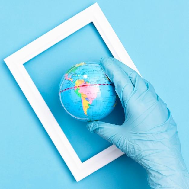 Vue De Dessus De La Main Avec Un Gant Chirurgical Tenant Le Globe Terrestre Dans Le Cadre Photo gratuit