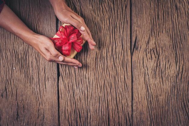 Vue de dessus main tenant une boîte cadeau sur fond de bois Photo gratuit