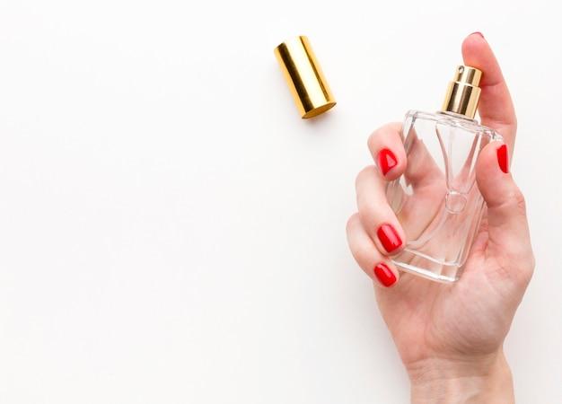 Vue De Dessus Main Tenant Une Bouteille De Parfum Avec Espace Copie Photo Premium