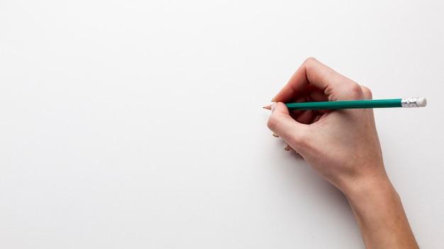 Vue De Dessus De La Main Tenant Un Crayon Avec Copie Espace Photo gratuit