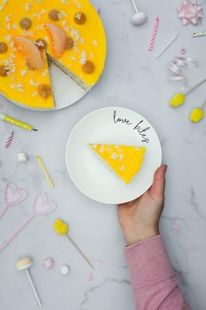 Vue De Dessus De La Main Tenant La Plaque Avec Une Tranche De Gâteau Photo gratuit