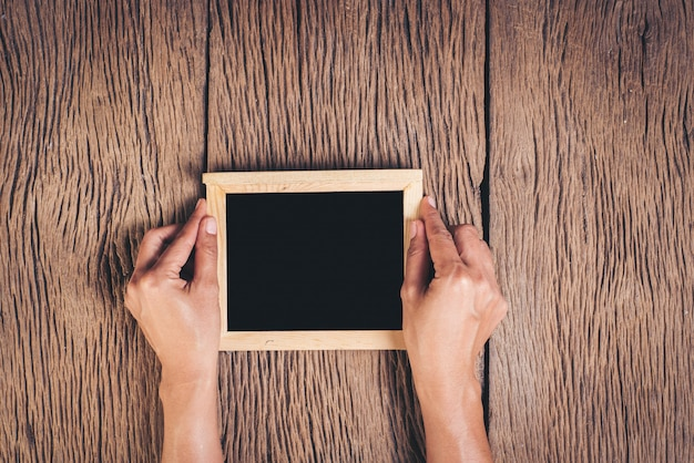 Vue de dessus main tenant un tableau sur fond de bois Photo gratuit