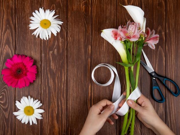 Vue De Dessus Des Mains Attachant Avec Un Ruban Un Bouquet De Fleurs Roses Et Blanches De Couleur Alstroemeria Et Calla Lys Sur Fond De Bois Photo gratuit