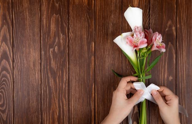 Vue De Dessus Des Mains Attachées Avec Un Ruban Un Bouquet De Fleurs Roses Et Blanches Alstroemeria Et Calla Lys Sur Fond De Bois Avec Espace Copie Photo gratuit