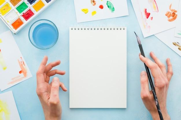 Vue de dessus mains et cahier entourés d'éléments de peinture Photo gratuit