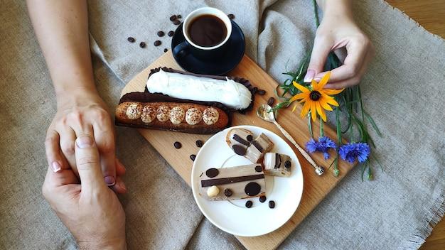 Vue de dessus des mains féminines et masculines se tenant près d'une tasse de café noir et servi éclairs Photo Premium