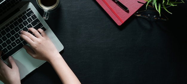 Vue de dessus des mains féminines avec ordinateur portable en tapant sur un bureau en cuir foncé et espace de copie Photo Premium