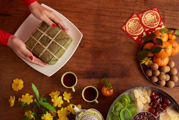 Vue de dessus des mains féminines servant un gâteau de riz Photo gratuit
