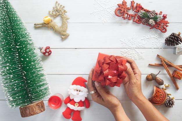 Vue De Dessus Des Mains De Femme Tenant La Boîte De Cadeau De Noël Sur Le Dessus De Table En Bois Blanc Photo Premium