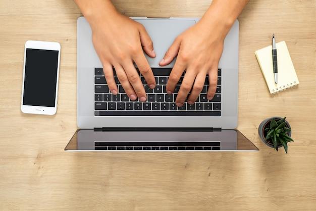 Vue de dessus des mains humaines travaillant sur un ordinateur portable moderne, surfer en ligne, taper un texte, naviguer sur internet Photo Premium