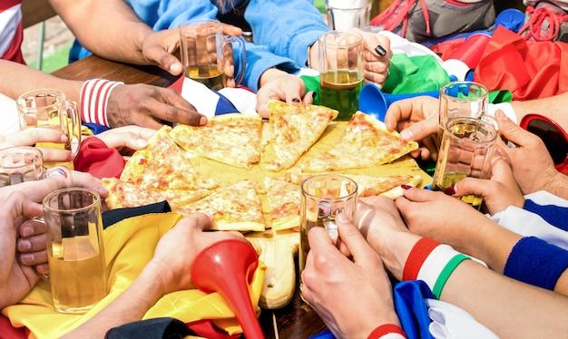 Vue de dessus des mains multiraciales d'un supporter d'amis de football partageant une pizza margherita au restaurant Photo Premium