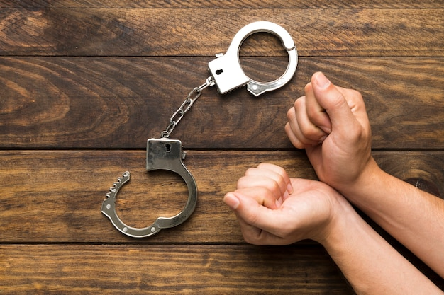 Vue de dessus des mains plaidant coupable avec des menottes Photo gratuit