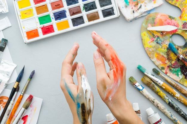 Vue de dessus mains sales avec du matériel de peinture Photo gratuit