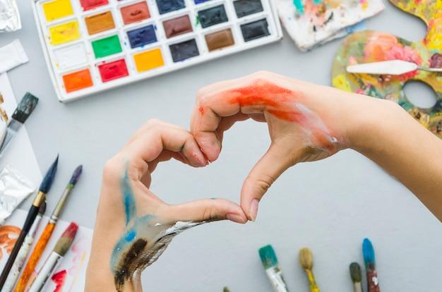 Vue de dessus des mains sales faisant un coeur avec du matériel de peinture Photo gratuit