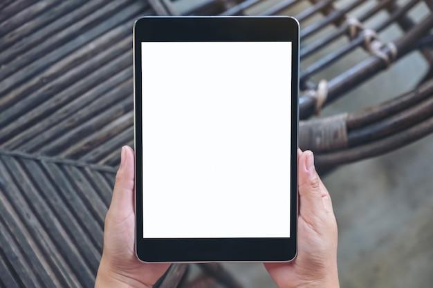 Vue De Dessus Mains Tenant Et à L'aide De Tablet Pc Noir Avec écran De Bureau Blanc Vierge Alors Qu'il était Assis En Plein Air Photo Premium