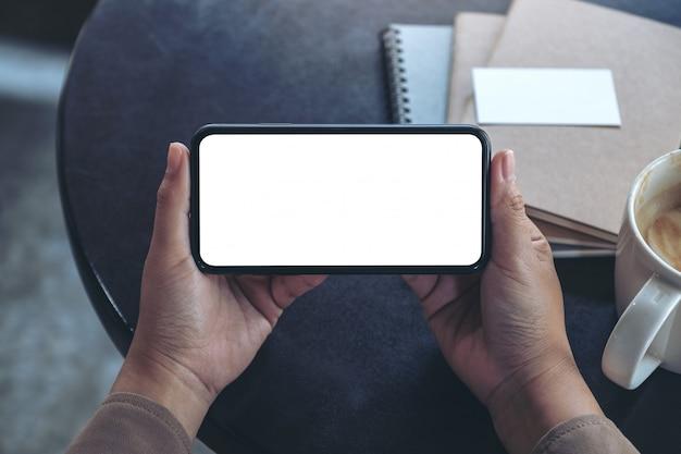 Vue De Dessus Les Mains Tenant Et à L'aide D'un Téléphone Mobile Noir Avec écran Blanc Horizontalement Pour Regarder Avec Une Tasse De Café Et Des Cahiers Sur La Table Photo Premium
