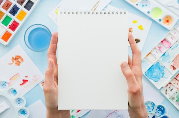 Vue de dessus mains tenant un cahier entouré d'éléments de peinture Photo gratuit