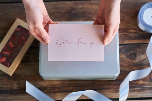 Vue De Dessus Des Mains Tenant La Carte De Voeux Avec La Phrase Française Qui Signifie Je T'aime Très Bien Préparé Pour Chérie Photo Premium