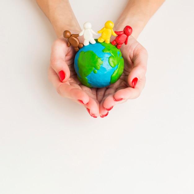 Vue De Dessus Des Mains Tenant Le Globe Avec Des Figurines De Personnes Photo gratuit