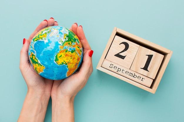 Vue De Dessus Des Mains Tenant Le Globe Terrestre Avec Calendrier Photo gratuit