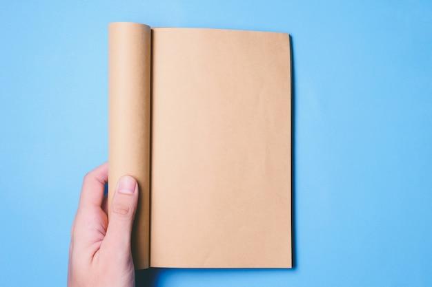 Vue de dessus des mains tenant un livre blanc prêt avec espace copie prêt pour le texte sur fond bleu. Photo Premium