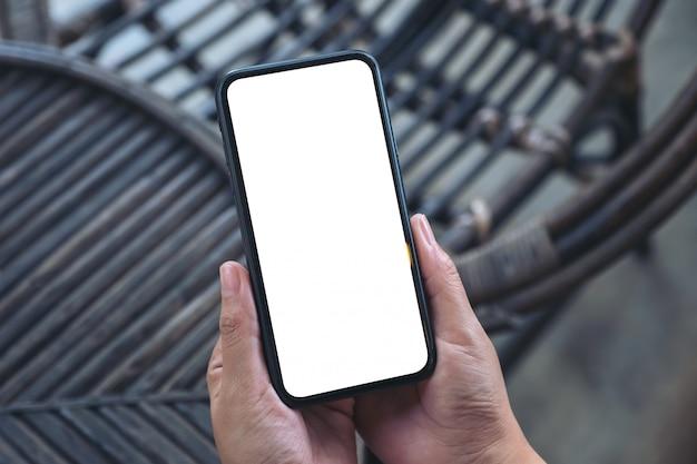 Vue De Dessus Mains Tenant Un Téléphone Mobile Noir Avec écran Blanc Vierge En Plein Air Photo Premium