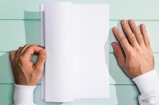 Vue de dessus mains en tournant les pages blanches vides Photo gratuit