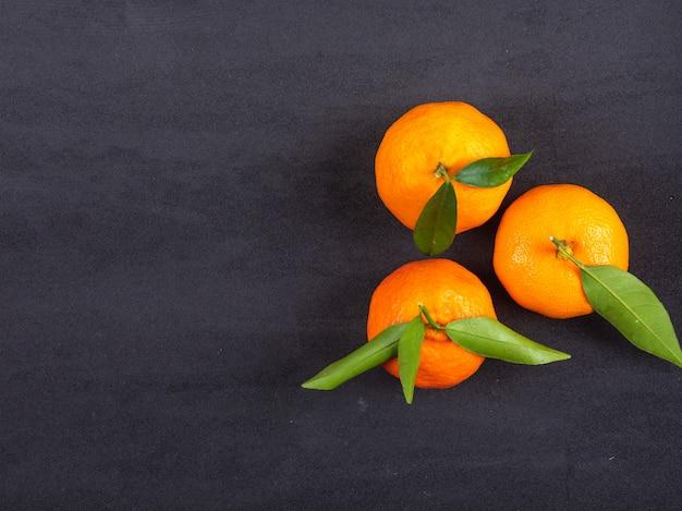 Vue De Dessus De Mandarines Fraîches Sur La Surface Noire Photo gratuit