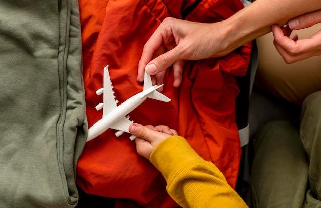 Vue De Dessus De La Mère Et De L'enfant Mettant La Figurine D'avion Dans Les Bagages Photo gratuit