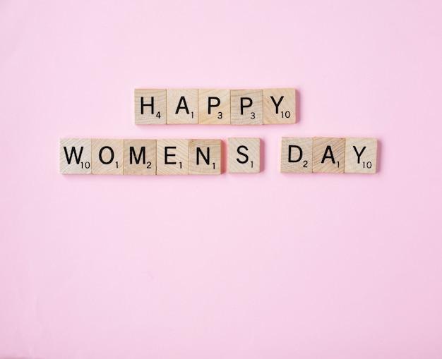 Vue de dessus message woomans jour heureux orthographié dans des blocs de bois sur fond rose Photo Premium