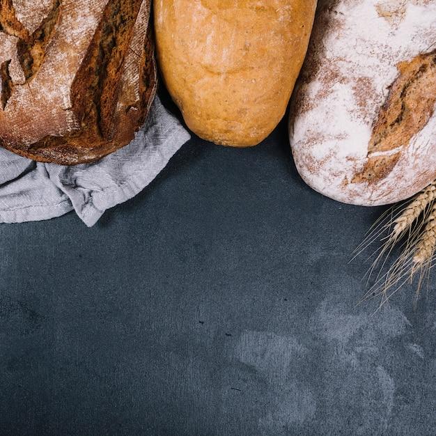 Une vue de dessus de miche rustique de pains sur le comptoir noir Photo gratuit