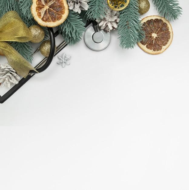 Vue De Dessus Mise En Page Médicale De Noël Avec Stéthoscope, Clip Board Et Arbres De Noël Avec Des Boules Et Des Cloches Photo Premium
