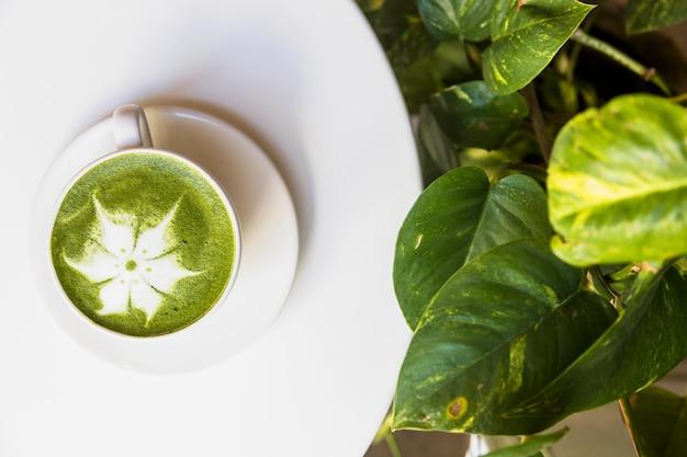 Vue de dessus de la mousse de thé vert matcha chaud sur un tableau blanc avec des feuilles vertes Photo gratuit
