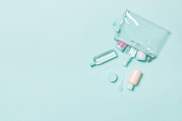Vue de dessus des moyens pour les soins du visage: bouteilles et pots de tonique, eau démaquillante micellaire, crème, cotons-tiges sur fond bleu. soins du corps avec espace vide pour vos idées Photo Premium