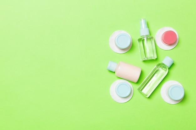 Vue de dessus des moyens pour les soins du visage: bouteilles et pots de tonique, eau démaquillante micellaire, crème, cotons-tiges sur vert. composition à plat avec fond Photo Premium