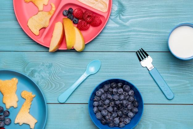 Vue De Dessus Des Myrtilles Et Des Aliments Pour Bébé Sur Une Assiette Avec Des Couverts Photo gratuit