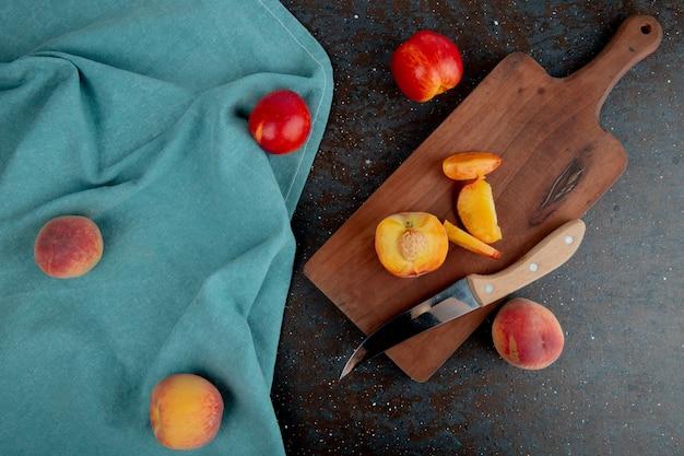 Vue De Dessus De La Nectarine Mûre Fraîche Et Des Tranches Avec Un Couteau De Cuisine Sur Une Planche à Découper En Bois Sur Tissu Bleu Sur Fond Noir Photo gratuit