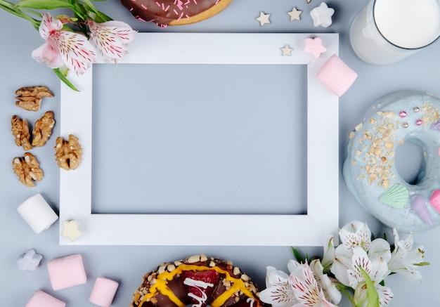 Vue De Dessus Des Noix Avec Des Bonbons Biscuits Au Lait Et Des Fleurs Sur Pourpre Avec Copie Espace Photo gratuit