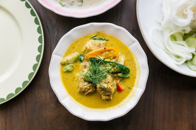 Vue De Dessus Des Nouilles De Riz Avec Sauce Au Curry Et Chair De Crabe, Servies Avec Des Légumes. Cuisine Thaïlandaise Classique. Photo Premium