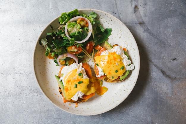 Vue de dessus de l'oeuf benedict au saumon et avocat, servi avec salade dans une assiette blanche. Photo Premium